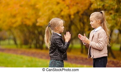 Little adorable girls having fun at warm day in autumn park...