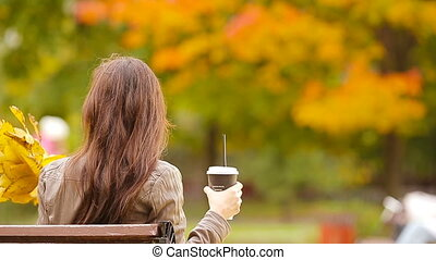 Beautiful woman drinking coffee in autumn park under fall...
