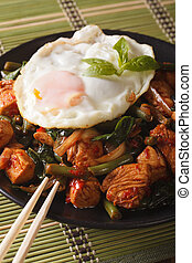 Thai chicken with basil and egg close-up on a plate vertical...