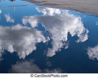 Reflection of white clouds in a puddle in a city street...