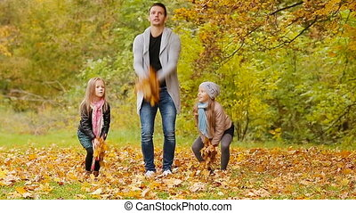Happy family having fun and throwing leaves around on an autumn day outdoors
