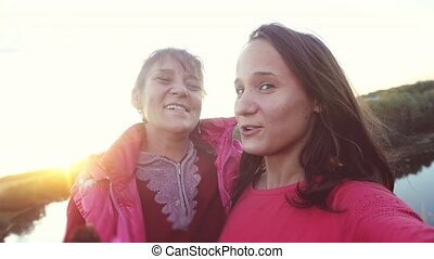 portrait of mother and daughter hugging laugh dancing and...
