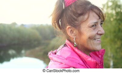 Portrait of smiles mature woman in age on the cliff with...