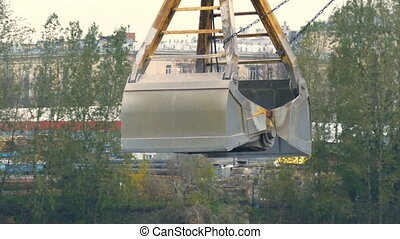 Excavator bucket is gaining the rubble from iron container on the background of the river