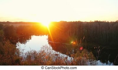 Beautiful landscape on the rock, a forest and a river. Reflected in the water the sun. sunset time with lens flare effect in slowmotion. 1920x1080