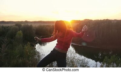 Young successful woman on top of the mountains dancing laughing excited look through the sun at sunset on the rock in slow motion.