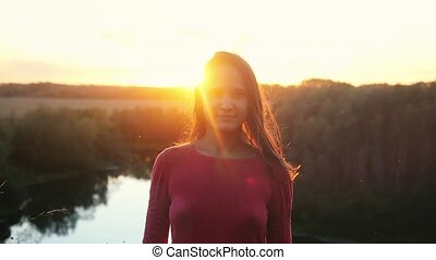Portrait of pretty young woman smiling at sunset in slowmotion.