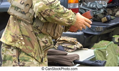The soldier puts equipment - Soldier puts the equipment to...