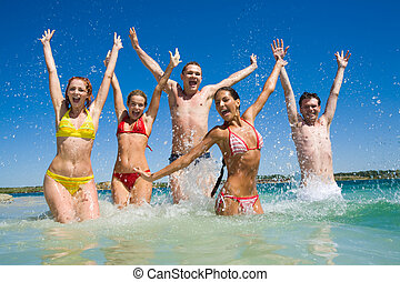 Playing in water - Image of happy teens playing in lake...