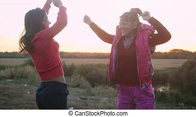 Mother and daughter dancing laughing and play the fool on a...