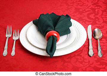 closeup of christmas dinner setting on red tablecloth