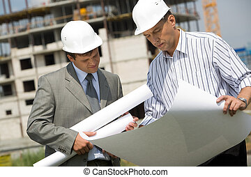 Teamwork - Image of businessmen looking at architectural...