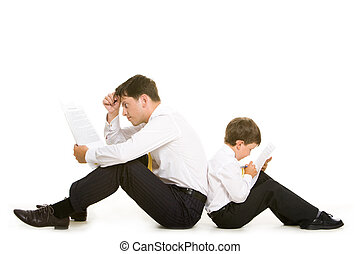 Intellectual work - Photo of father and son sitting aback to...