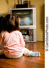 Watching TV - Rear view of little girl sitting on the floor...