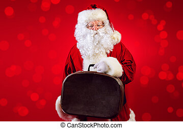 tourist santas - Santa Claus stands with old suitcase over...