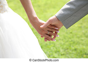 Togetherness - Close-up of bride?s hand holding that of her...