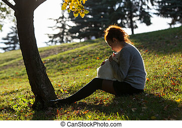 young lady with Maine Coon cat seats on the grass