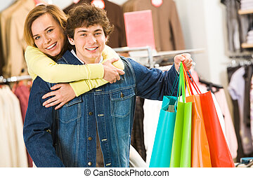 In the mall - Attractive woman embracing her boyfriend with...