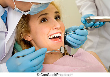 Teeth cure - Image of young lady with dentist over her...