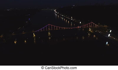 Aerial View of European City at Night with Illuminated Light from Cars, Colorful Bridge Over the River.