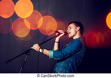Young Man Singing with Microphone.