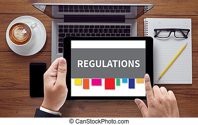 REGULATIONS, on the tablet pc screen held by businessman...
