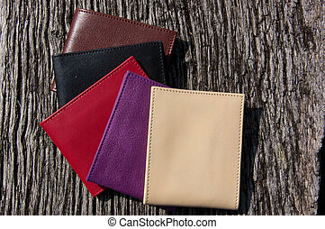 Leather wallets on a wooden table as background