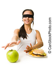 Choosing healthy food - Portrait of young girl in blindfold...