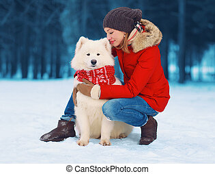 Christmas, winter and people concept - happy young woman owner petting embracing white Samoyed dog on snow