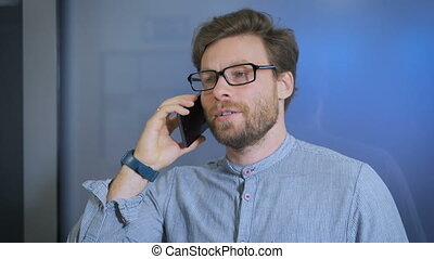 Young man talking on cell phone at modern office
