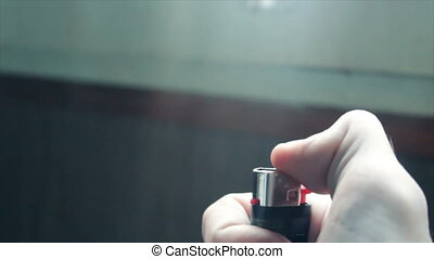 burning lighter in the hand of a young man