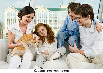 Staying at home - Photo of cute girl caressing pet on her...