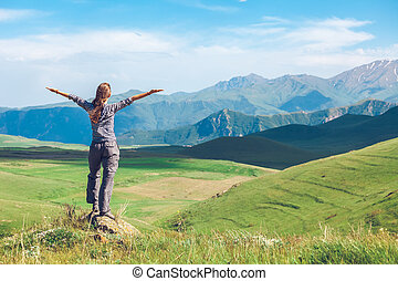 woman with raised hands on hills