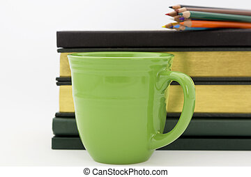 Academic work and study - Green mug in front of books with...