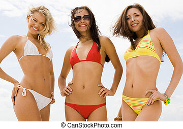 Three girls - Portrait of three slim girls in bikini smiling...