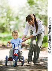 Riding bicycle - Lovely woman touching her son while he...