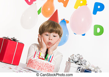 Blowing on candles - Portrait of happy boy blowing on...