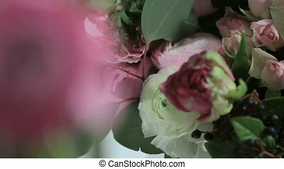 Camera shoots flowers of the roses, bouquet in motion.