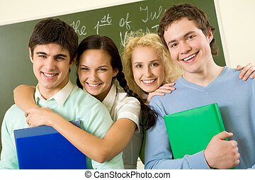 Happy teens - Portrait of happy students standing next to...
