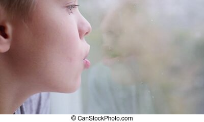 Child draws a finger on the window glass. Snow outside in blur