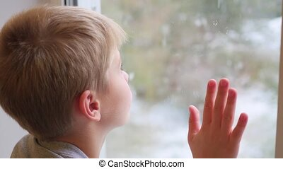 a child looks out the window at the snowfall - The child...