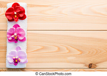 terry a napkin and three orchids on wooden boards