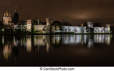 Night view illuminated Novodevichy Convent of Our Lady of Smolensk is reflected in the water of the nearest pond. Moscow, Russia