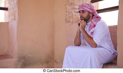Young arabic man sitting and thinking about something