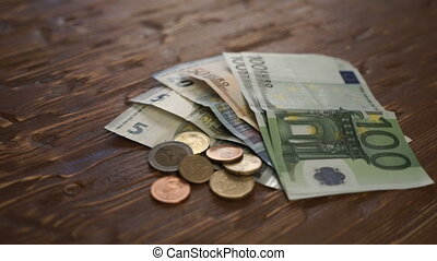 Euro Bills and Coins turn around. - Euro Bills and Coins on...