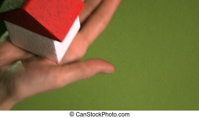Woman holding toy house with red roof against green...