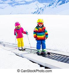 Child on ski lift - Children on magic carpet ski lift going...