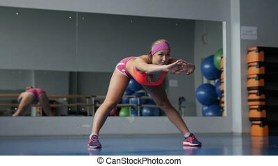 Warming up before training. Young woman in sportswear doing stretching while standing in front of window at gym.