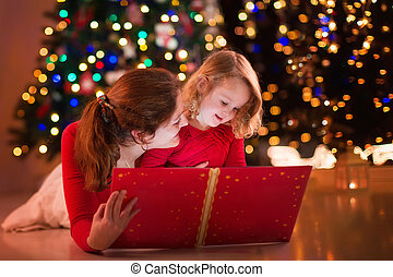 Mother and daughter reading at fire place on Christmas eve -...