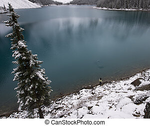 Girl skipping rocks on the shore of a blue lake in the snow